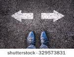 stock-photo-feet-and-two-arrows-painted-on-an-asphalt-road-329573831